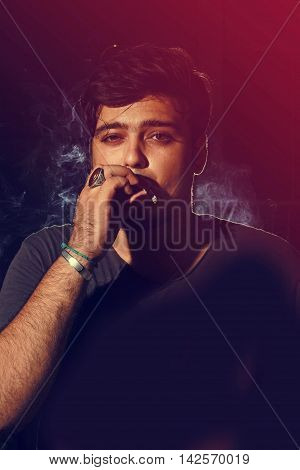 Young man smoking cigarette on dark background looking into camera wearing t shirt