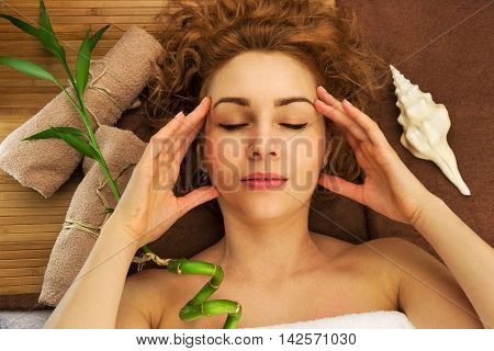 Spa concept from beautiful young woman with curly hair, shell, bamboo and towels, close eyes