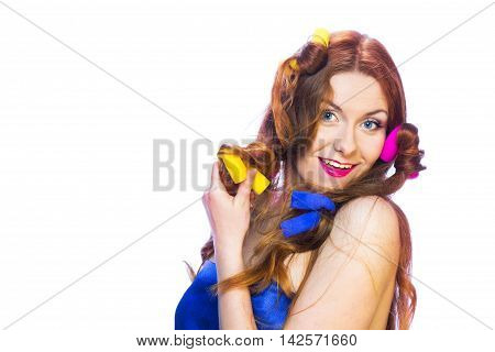 Pretty smiling woman in colorful curlers isolated on white background