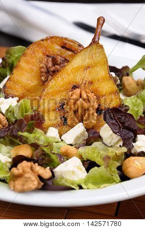 Salad of lettuce with walnuts cashews slices feta halves of caramelized pear