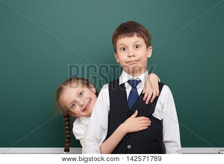 two school student posing at the clean blackboard, grimacing and emotions, dressed in a black suit, education concept, studio photo