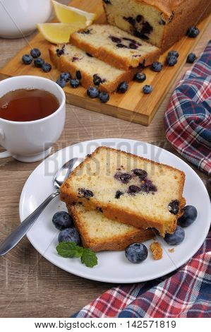 sliced summer cake with blueberry with a cup of tea on the table