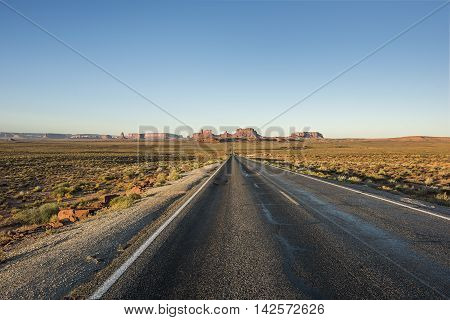 View of Monument Valley canyons during sunrise with Road in Arizona