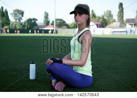 Sporty girl drinking from a bottle. Football stadium. Slim sporty fitness woman. Bottle Shaker protein. Social media and fitness concept. Toned image.