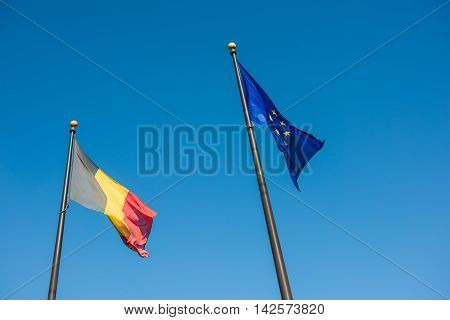 Belgian and European Union flags against blue sky