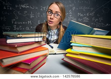 student sitting at a desk full of books,  shocked expression
