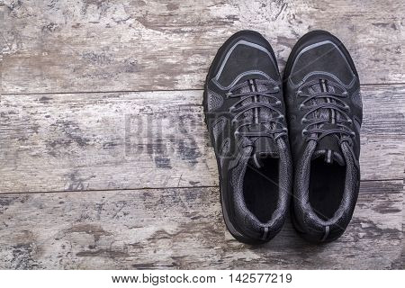 Hiking shoes laid on a wooden floor background