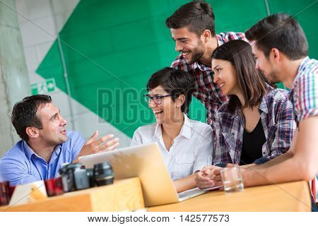 Businessman talking with young people in coffee shop