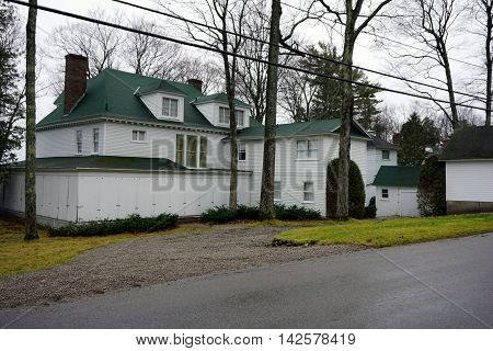 WEQUETONSING, MICHIGAN / UNITED STATES - DECEMBER 23, 2015: A large white home, on Beach Road in Wequetonsing, is boarded up for the winter weather.