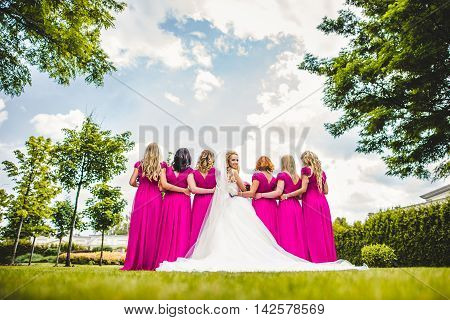 Bride with bridesmaids in a park on the wedding day