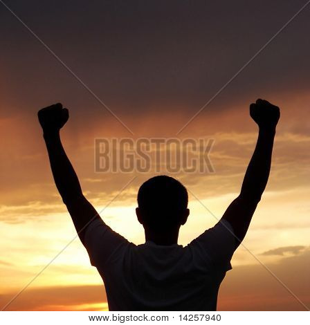 A man stands on against a sun with heaved up hands