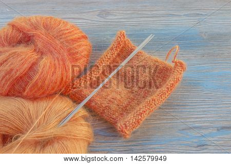Knitting orange mohair wool and needles on wooden blue rustic background. The beginning on knit cloth