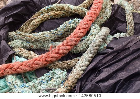 Multi-colored fishing ropes on black polyethylene. Fragment of fishing tackles