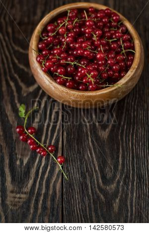 Fresh red currants in plate on wooden table