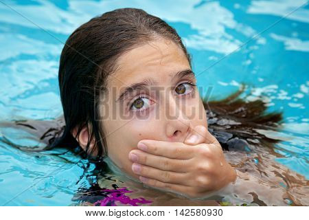A tween girl in a swimming pool covers her mouth with her hand. She is embarrassed to have her crooked teeth show in pictures. She looks a bit surprised or scared.