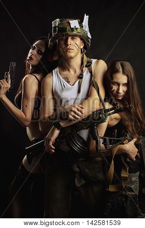 Young armed guy and two military girls with guns posing over dark background