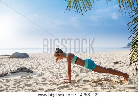 Young Pretty Slim Brunette Woman Practise Yoga Pose On Tropical Beach