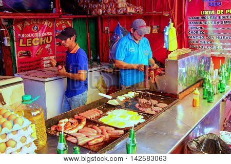 ASUNCION PARAGUAY - DECEMBER 26: Unidintified men cook at the food stall at Mercado Cuatro on December 26 2014 in Asuncion Paraguay. Asuncion is the capital and the largest city of Paraguay