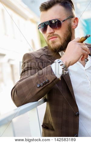Handsome brunette man in sunglasses and with cigarette in his hand outdoors