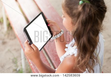 Little girl holding a tablet . Blank screen . technology and internet concept