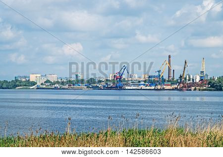 Provincial industrial river port on the background of cloudy sky
