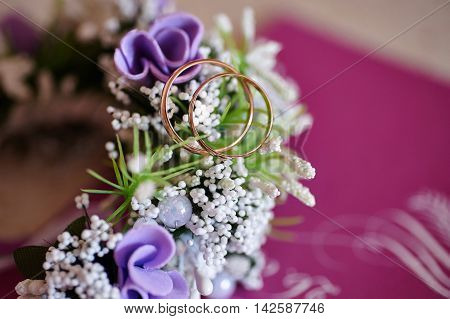 wedding boutonniere of flowers and golden rings.