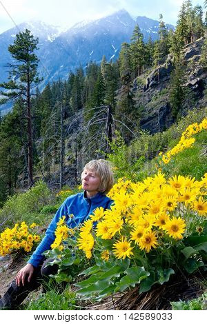 Woman sitting in grass among yellow flowers. Fourth of July Trail near Leavenworth and Seattle Washington state USA.