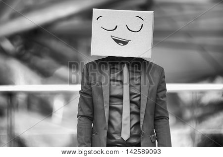 Young Man Standing A Cardboard Box On His Head With Smiley Face