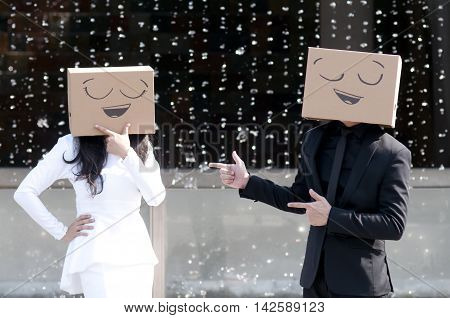 Young Woman And Young Man Standing And Gesturing With A Cardboard Box On Her Head With Smiley Face