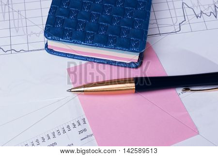 Pen lying on financial statements. Business Background