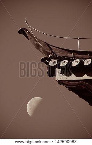 Old roof and moon in Lijiang, Yunnan, China.