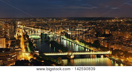 Paris city skyline rooftop view with River Seine at night, France.