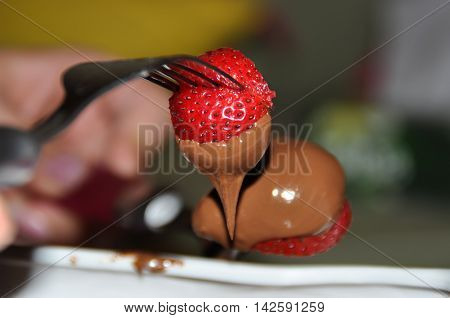 Strawberries Dipped In Chocolate On A Fork