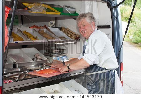 Friendly Smiling Man Serving Fresh Fish From A Mobile Van