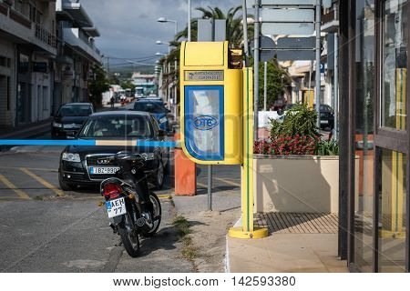 SITIA, CRETE, GREECE - JUNE 2016: Old yellow telephone booth at street of Chania town on Crete island. OTE is the Hellenic Telecommunications Organizatio