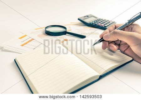 Hand working with business paper documents with calculator and magnifying glass in background. Photo with warm tone.