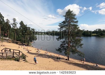 ROSCHINO, LENINGRAD REGION, RUSSIA - JULY 10, 2016: People resting on the beach at lake Roschinskoe. The pond was created by the small hydro-power plant which was built here in 1898-1899