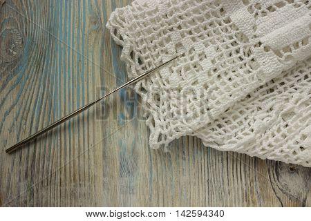 Handmade crocheted cotton organic blanket on wooden background. Old crocheting hook