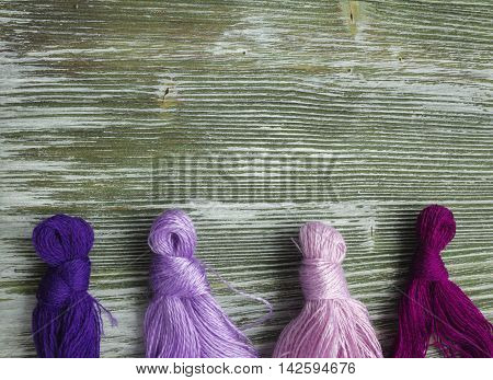 Bright wool thread for embroidery and needlework. Sewing threads for embroidery. Mouline floss on rustic wooden table