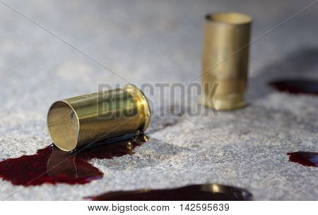 Pistol brass that is on concrete with blood around