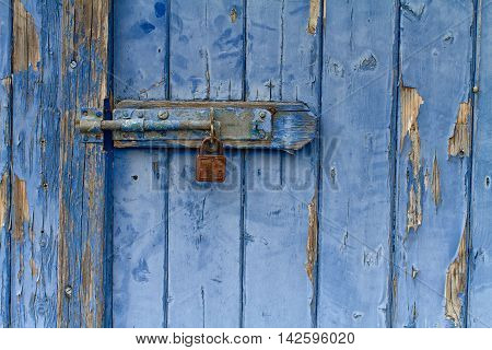 Flaking Blue Painted Wooden Door With Rusty Padlock