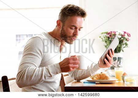Older Man Drinking Coffee With Breakfast And Holding Tablet