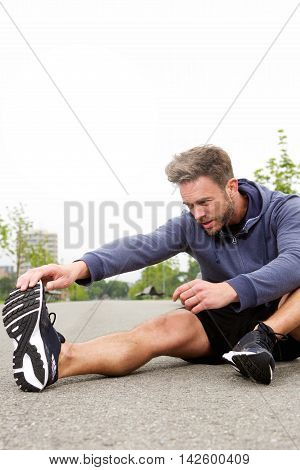 Determined Runner In The Middle Of Stretch For Workout Routine