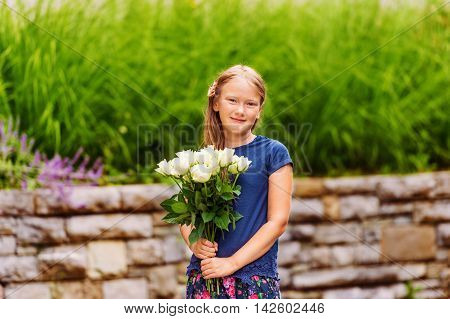Outdoor portrait of a yong little girl of 9 years old, wearing blue tee shirt, holding fresh bouquet of beautiful white roses