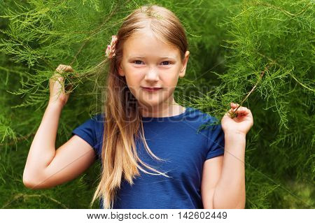 Outdoor portrait of a cute little girl of 8-9 years old playing in the park