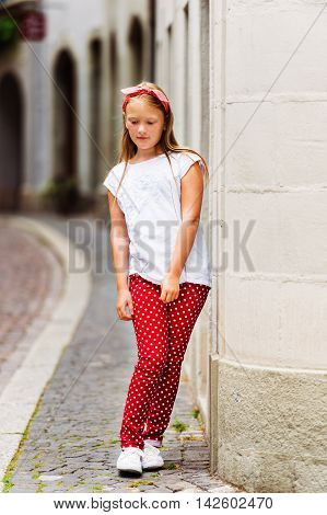 Outdoor fashion portrait of a ute little girl of 8-9 years old walking down the street, wearing polkadot trousers and white tee shirt