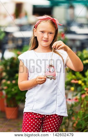 Outdoor fashion portrait of a cute little girl of 8 years old, wearing funny headband, white tee shirt and polka dot trousers