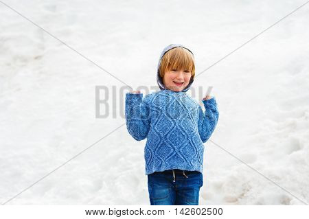 Winter portrait of a cute little boy of 4 years old, wearing blue knitted pullover
