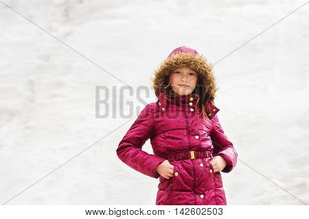 Winter portrait of a cute little girl of 7 years old, wearing maroon jacket
