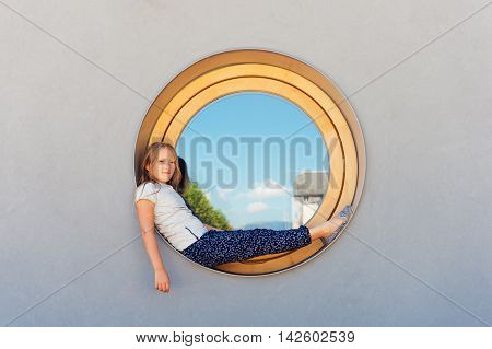 Funny little girl sitting on a round window outdoors